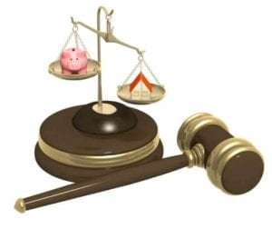Scales of justice sitting on top of a judge's gavel, weighing a piggy bank and a house.