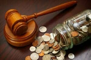Money jar with coins spilling out next to a judge's gavel.