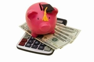Piggy bank with a graduation cap sitting atop a calculator and money.