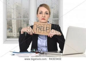 """Sad business woman holding a """"Help"""" sign as she sits at her computer."""