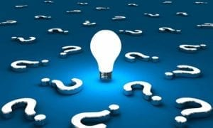 Illuminated light bulb on a blue background full of question marks