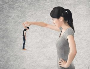 Asian woman holding a miniature Asian man, looking at him with blame