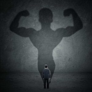 Shadow of a small businessman is a big muscle man