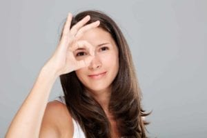 Womanmaking positive finger geseture in front of her eye
