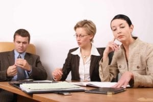 Unhappy man and woman sit at a business table with a divorce mediator.
