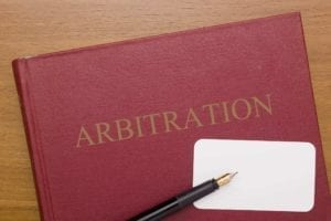 "Red book with the word ""Arbitration"" on it with a blank business card and a pen."