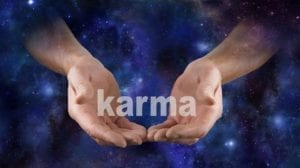 "Hands on a mystical background holding the word ""Karma."""