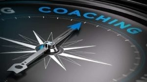 "Close up of compass pointing to the word ""Coaching."""