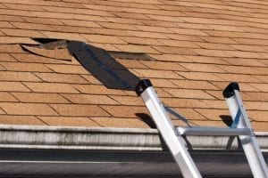 A ladder rests on a gutter next to missing shingles on a roof.
