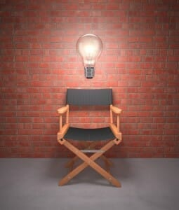 Empty director's chair against a brick wall with a giant, lit light bulb over it.
