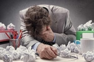 Exhausted business man holding his head. He sits at a table overflowing with wadded up papers.