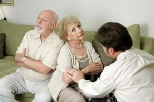 Angry older couple with their son trying to mediate their argument