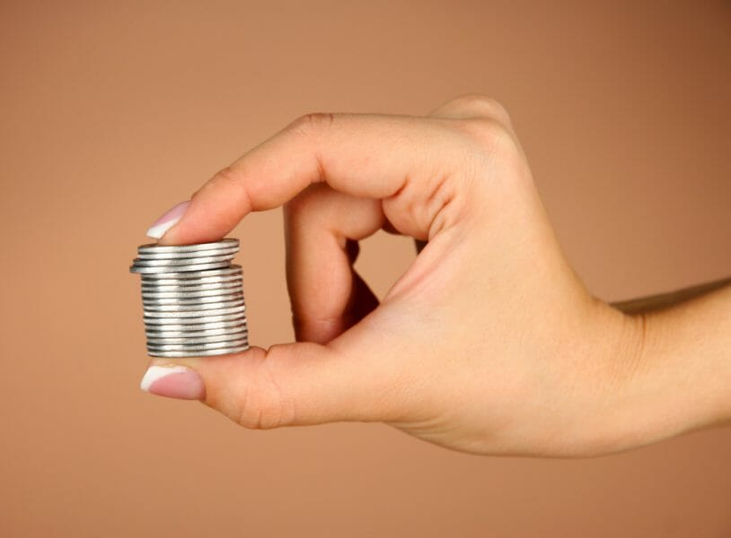Close up of a woman's hands holding a stack of silver coins.