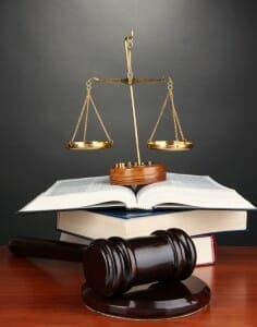 Scales of justice sitting on law books with judge's gavel nearby