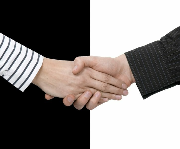 Man and woman's hands in a handshake in front of a black and white background.