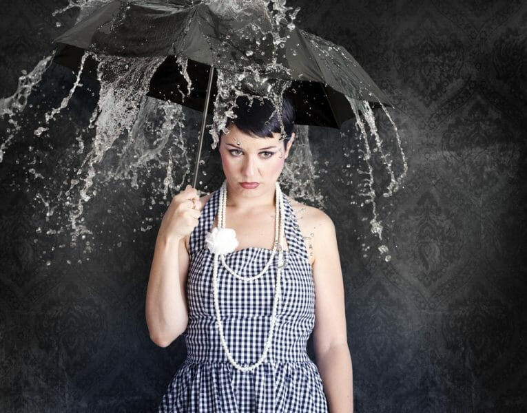 Sad young woman in a dress holding an umbrella over her head as water pours down.