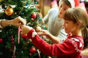 Happy children decorate a Christmas tree.