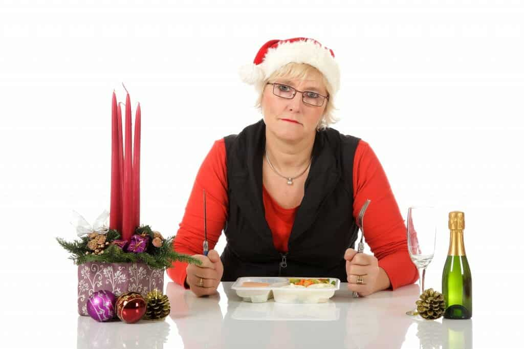 Despondent woman in Santa hat eating a TV Dinner alone.