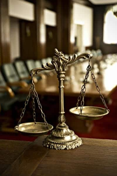 Close up of unbalanced scales of justice with a court room in the background