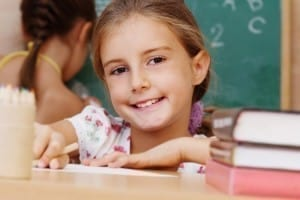 Smiling young girl with a good parenting plan sitting in school.