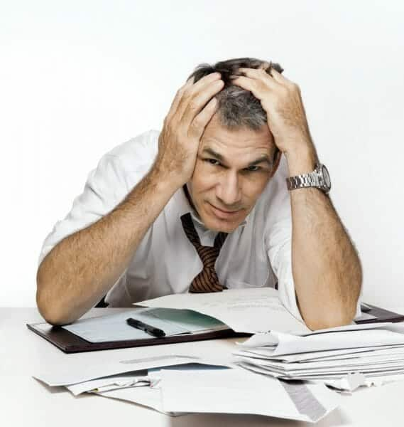 Harried man with a pile of bills and paperwork in front of him, holding his head.