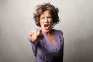 Angry screaming woman pointing directly at the camera.