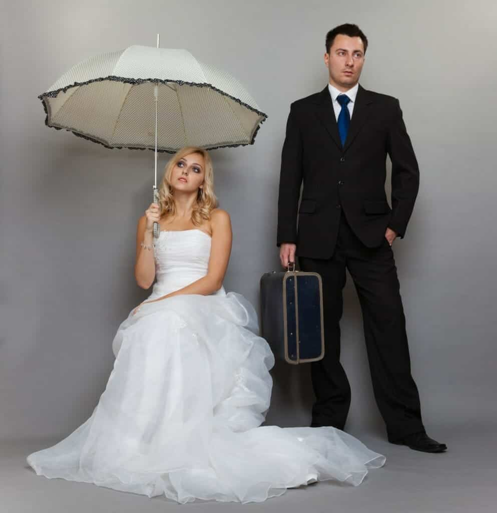 Bored bride sitting down holding an umbrella over her head while groom holding a suitcase looks away.