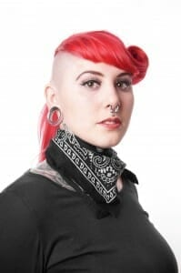 Woman with half-shaved head, pink hair, big ear loops, a nose ring and piercings.