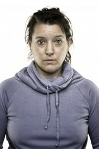 Woman with dirty hair and no makeup wearing a hoodie.