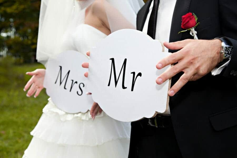 """Bride and Groom holding signs """"Mr."""" and """"Mrs."""""""
