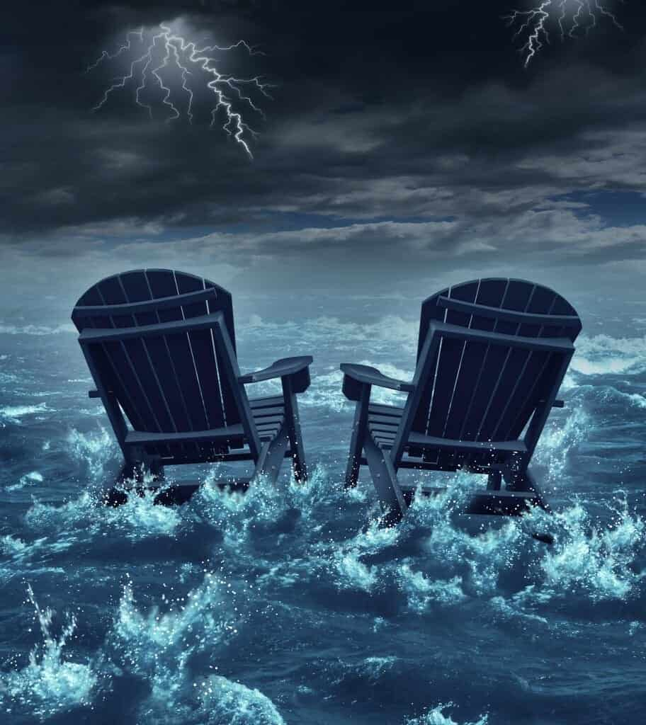 Two adirondack chairs on the beach in the rising time with a lightning storm going on.