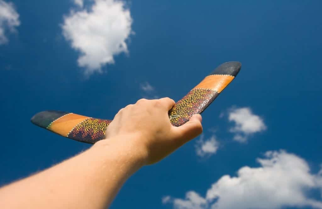 Close up of a hand holding boomerang up to the sky.