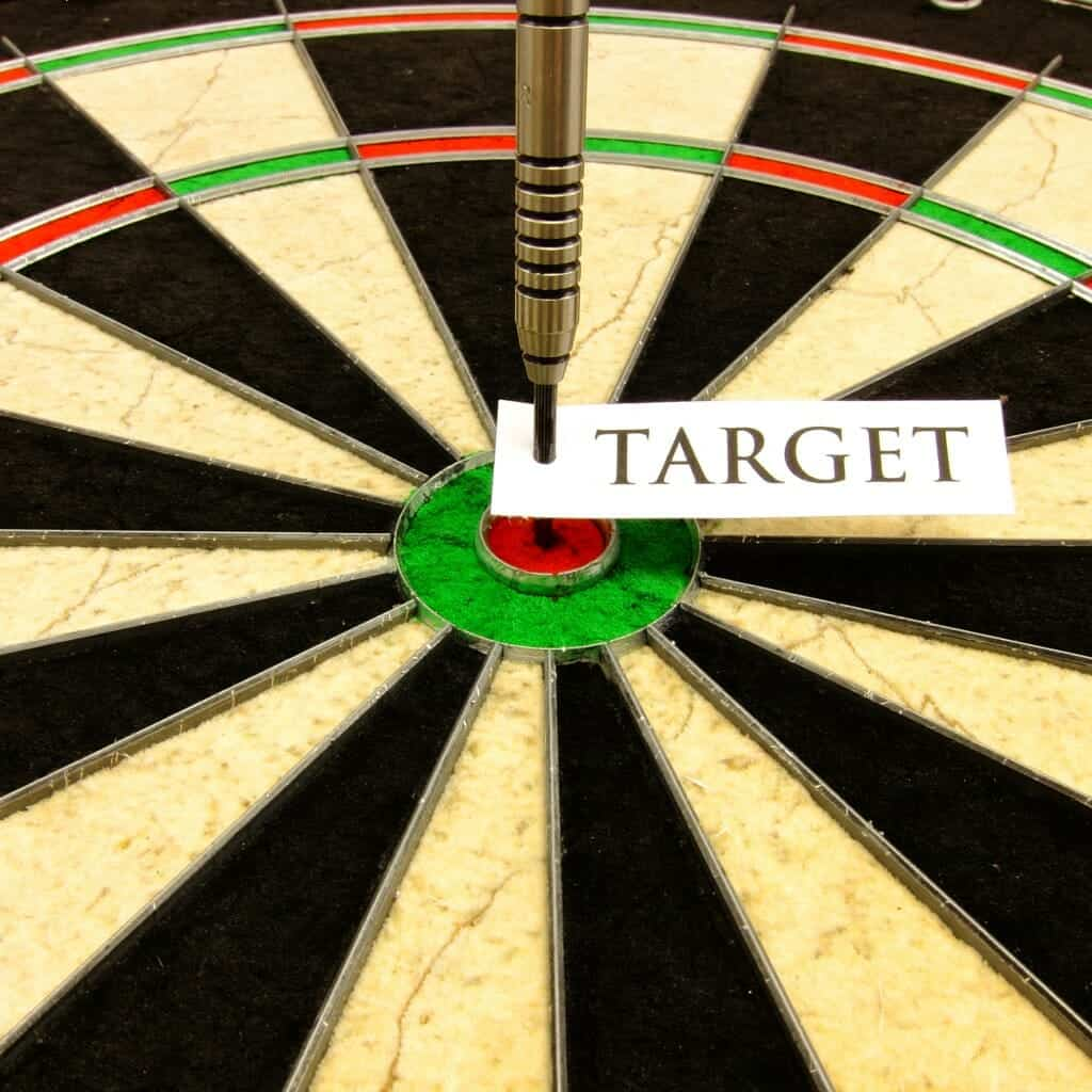 "Close up of a dart board with a dart standing up in the bull's eye with a note that says ""Target"" on it."