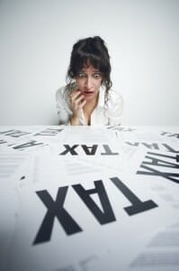 "Scared woman looking at papers on a desk that say ""Tax"" in big letters."