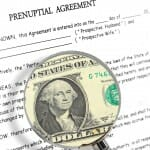 Prenuptial agreement with a magnifying glass over it showing dollar bill