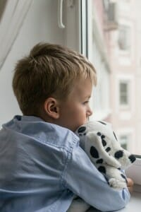 Sad boy holding a stuffed toy and looking out the window.