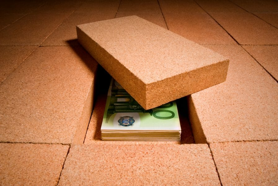 Stack of money hidden under a brick in a brick floor.