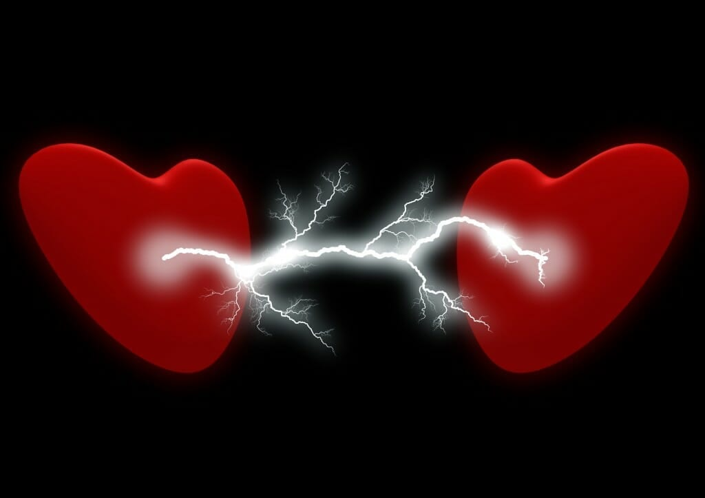 Two red hearts with lightning/electricity between them. It is ripping one heart.
