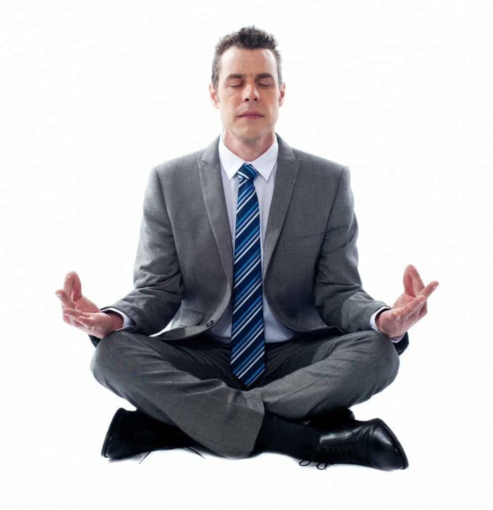 Business man sitting in lotus position, meditating.