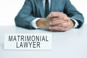 """Attorney sitting at a table with a sign """"Matrimonial Lawyer."""" Should you change attorneys during your divorce?"""