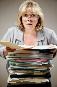 Harried woman holding a large stack of divorce financial documents.