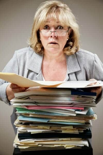 Harried woman holding a large stack of paperwork.