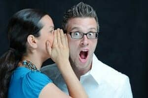 "Woman gossips into a surprised man's ear. What will ""they"" say if you divorce?"