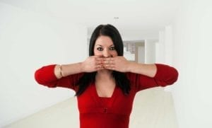 Woman with her hands covering her mouth. She doesn't want to make divorce announcements.