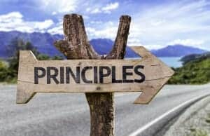 "Wooden arrow sign with the word ""Principles"" on it"