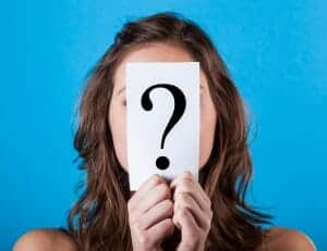 woman holding a paper with a question mark in front of her face.