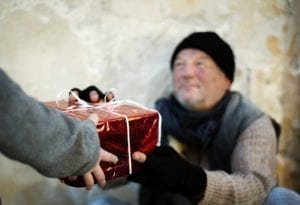 Homeless man accepting Christmas present. Live the Christmas spirit.