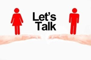 "Hands holding man and woman figures with the words ""Let's Talk"" between them"
