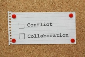 Note paper on a cork board with a list depicting choice between conflict and collaboration.