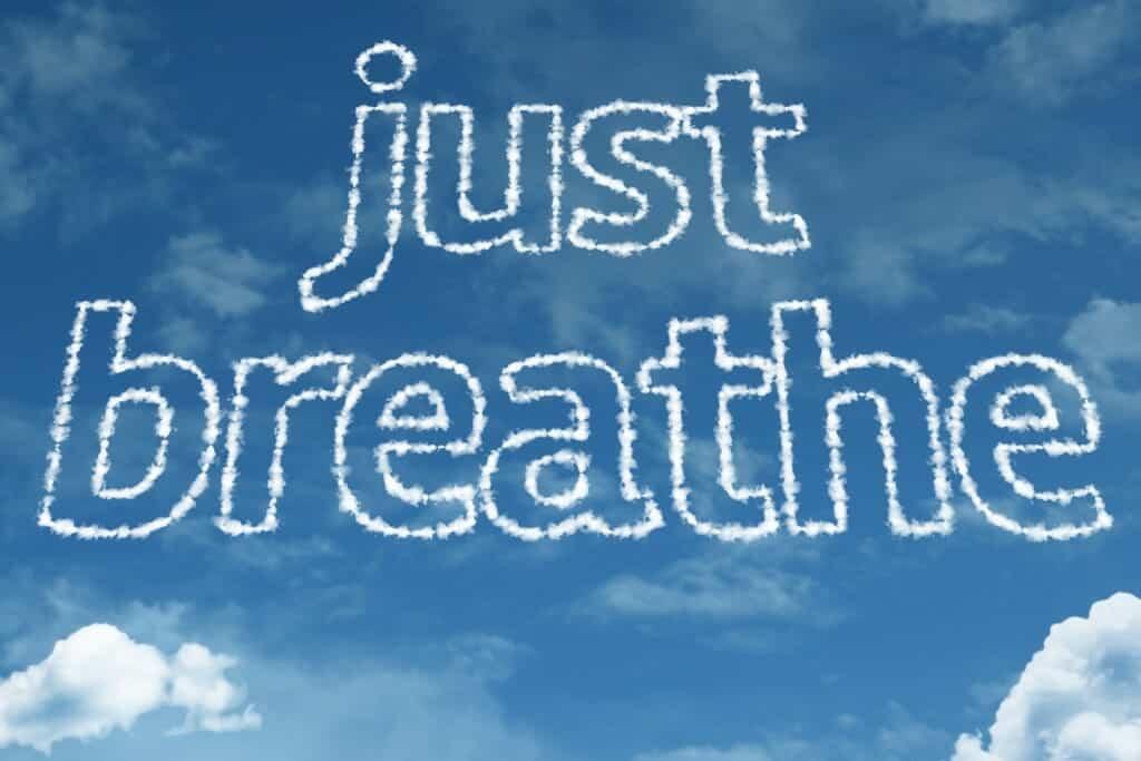 """Just breathe"" written in clouds on a blue sky."